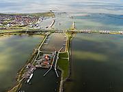 Nederland, Noord-Holland, Gemeente Wieringen, 16-04-2012; Den Oever, begin Afsluitdijk, gezien naar het noordoosten. Aan de horizon is de kust van Friesland zichtbaar. De 32 kilometer lange dijk vormt de waterkering tussen Waddenzee (links) en IJsselmeer (rechts). In de dijk de Stevinsluizen (spuisluizen of uitwateringssluizen). In de voorgrond de schutsluis voor de scheepvaart. Aanleg van de dijk vormde onderdeel Zuiderzeewerken, initiatief van ingenieur Cornelis Lely..Den Oever, beginning Enclosure Dam, looking east. The Stevin sluices sluice surplus water to the Wadden sea, in the foreground the lock for vessels. Construction of the dam was part of the Zuiderzee Works, an initiative of engineer Cornelis Lely..luchtfoto (toeslag), aerial photo (additional fee required).foto/photo Siebe Swart.luchtfoto (toeslag), aerial photo (additional fee required).foto/photo Siebe Swart