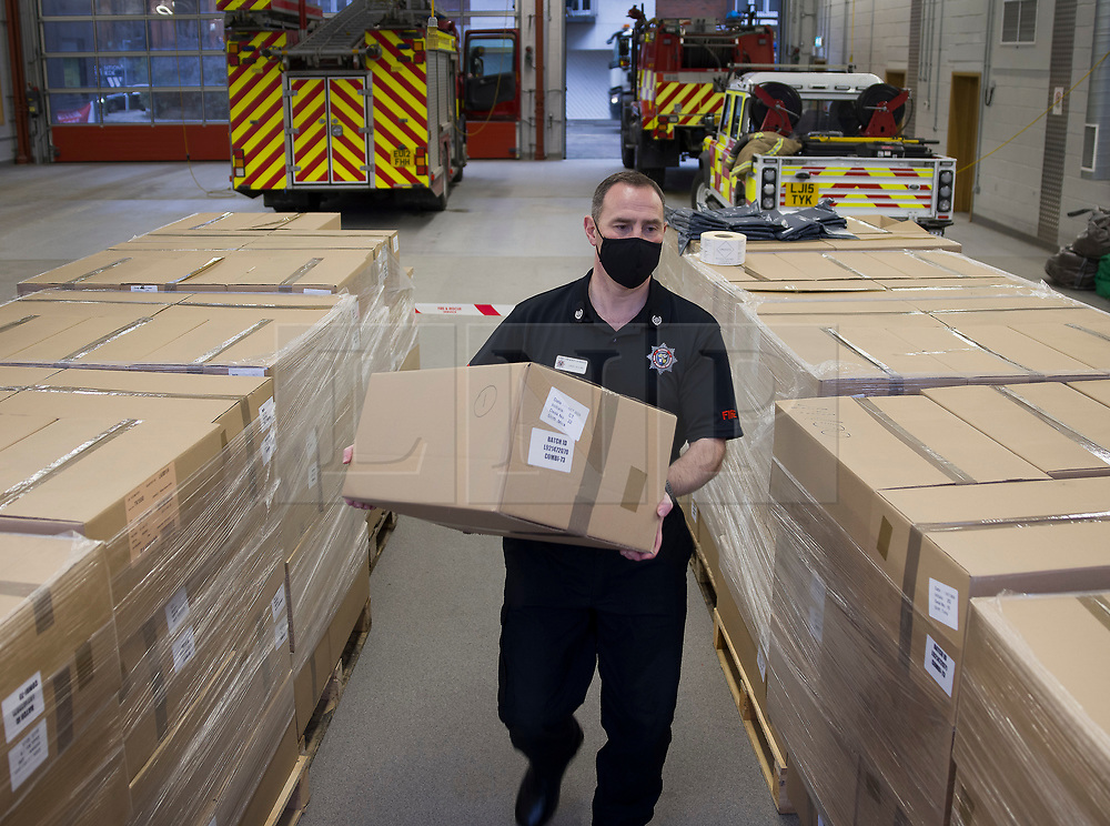 © Licensed to London News Pictures. 01/02/2021. Woking, UK. Fire Officer Group Commander David Nolan sorts some of the 10,000 Covid-19 test kits, at Woking Fire Station, ahead of their delivery to residents in the Goldsworth Park area in Surrey, where some cases of the South African variant of Covid-19 have been found. Public health England will carry out surge testing for selected parts of the Goldsworth Park, St Johns and Knaphill areas of Woking. Photo credit: Peter Macdiarmid/LNP