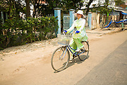 13 MARCH 2006 - CHAU DOC, AN GIANG, VIETNAM: A woman in a ao dai (traditional Vietnamese dress) rides her bicycle home from work in Chau Doc, Vietnam in the Mekong delta. The Mekong is the lifeblood of southern Vietnam. It is the country's rice bowl and has enabled Vietnam to become the second leading rice exporting country in the world (after Thailand). The Mekong delta also carries commercial and passenger traffic throughout the region.  Photo by Jack Kurtz