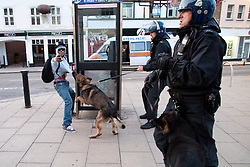 © Licensed to London News Pictures . FILE PICTURE DATED 07/08/2011. Enfield , UK . A man reaches out as a police dog bites his shirt . Riot police with dogs work to clear people from Enfield Town Centre as hundreds gathered and broke in to shops following messages sent via Blackberry Messenger . Following a night of riots and looting in Tottenham , looting spreads to other parts of London . Photo credit : Joel Goodman/LNP
