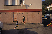Municipal housing Marseille. Racist grafitti adorns the walls. French Gitans, in the south of France, are full of spirit. They live as strong communal families with everyone looking after the children, living and breathing the rythmns of rhumba and flamenco music. Any chance to celebrate brings song and dance together with 'palmas' hand clapping. Some work the markets, others doing building, cleaning or maintenance work. Some live in municipal apartments others in caravans. They most often live within their own communities, distrustful of outsiders, and  experience problems of innercity life, and of racism. Roma people have suffered a history of racial persecution for centuries. Though mainly sedentary living in houses and apartments, they are still viewed from the outside as 'Les gens de voyage'. Many will holiday, take seasonal work or go to religious festival in their caravans, coming back to their house over for the rest of the year. Southern France