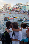 A couple embraces in front of the Rio Vermehlo. February 2nd is the feast of Yemnaja, a Candomble Umbanda religious celebration where thousands of adherants to these faith religions go to Rio Vermehlo Red River to make offerings of flowers and prayers, paying their respects to Yemanja, the Orixa goddess of the Sea and water