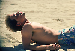 Shirtless man on the beach getting some sun