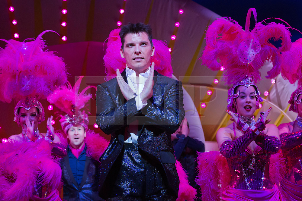 """© Licensed to London News Pictures. 21 March 2014. London, England. Pictured: Nigel Harman as Simon. Photocall for the Simon Cowell X-Factor Musical """"I Can't Sing!"""" written by Harry Hill and Steve Brown at the London Palladium. Directed by Sean Foley with Nigel Harman as Simon, Victoria Elliott as Jordy and Ashley Knight as Louis. Photo credit: Bettina Strenske/LNP"""