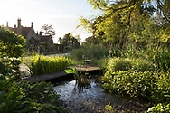A metal loveseat on a deck overlooking the moat, aquatic plants and tudor manor house, Hindringham Hall, Hindringham, Norfolk