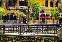 A woman rides her bike over a footbridge, Hoi An, Vietnam.