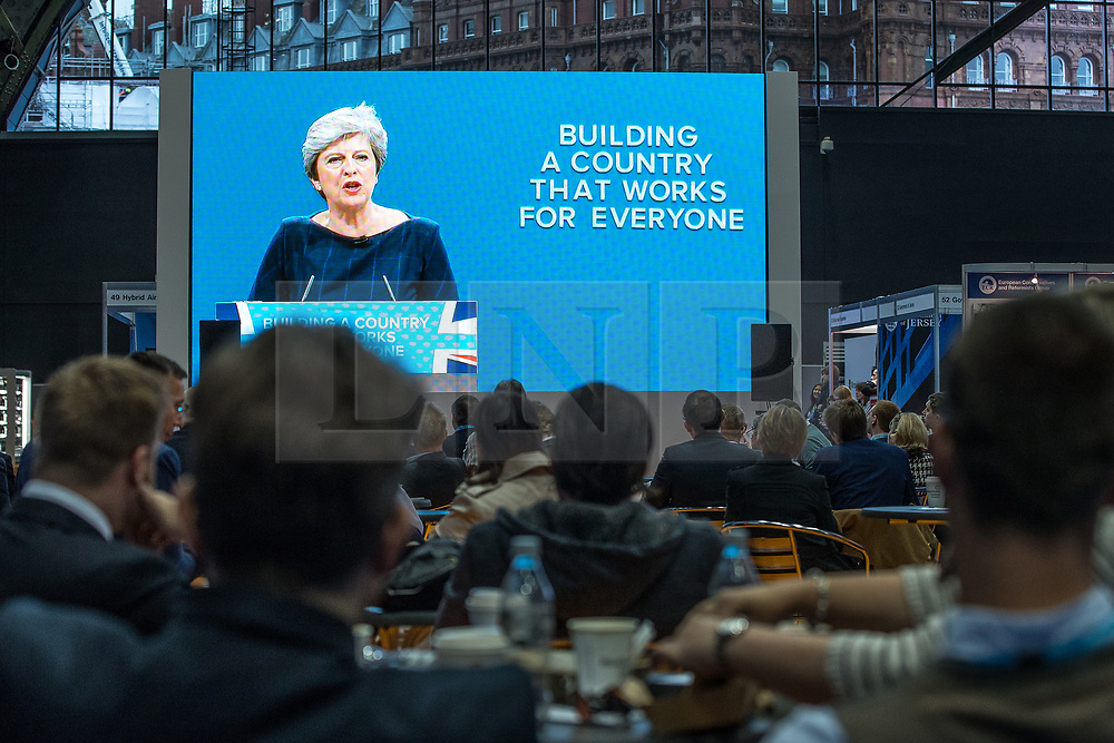 © Licensed to London News Pictures . 04/10/2017. Manchester, UK. Delegates watch Prime Minister THERESA MAY deliver her keynote speech on a big screen in the conference exhibition on the fourth and final day of the Conservative Party Conference at the Manchester Central Convention Centre . Photo credit: Joel Goodman/LNP
