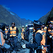 """Mountain Biking on Death Road, Bolivia...A tour group of Mountain Bikers stop to be briefed about the next stage of the journey by their tour leader...The North Yugas Road is a 64 Kilometer road leading from La Paz to Corioico. It is legendary for it's extreme danger and in 1995 the Inter American Development Bank christened is as the """"world's most dangerous road"""".. The road was built in the 1930's during the Chaco War by Paraguayan prisoners to connect the Amazon rainforest region of Northern Bolivia to it's capital City La Paz. One estimate is that 200 to 300 travelers were killed yearly along the road. On 24 July 1983, a bus veered off the Yungas Road and into a canyon, killing more than 100 passengers in what is said to be Bolivia's worst road accident..A new stretch of the La Paz-Coroico highroad was opened in 2006 to bypass the notorious stretch known as death road..The danger of the road has now made it a popular tourist destination starting in the 1990's and drawing thrill-seekers and mountain bike enthusiasts who ride on the 64km mainly downhill stretch from La Cumbre, a 4,700 meter peak to Yolosa, a decent of 3600 meter's (11,800 feet). The journey includes breathtaking views of snow covered peaks and towering cliffs and starts along modern asphalted road before entering the jungle itself and the most dangerous and notorious part of the ride. The infamous narrow dirt road, most of the road no wider than 3.2meter's, is cut into the side of the mountain with sheer drops to the left of up to 600 meter's with virtually no safety rails on the winding steep decent..There are now many tour operators catering to this activity, providing information, guides, transport and equipment. Nevertheless, the Yungas Road remains dangerous. At least 13 of these cyclists died on the ride since 1998, the latest A 28-year-old Israeli traveler was killed in April 2010  the group of cyclists arrived at a heavily foggy area. The woman got separated from the group, and fell into a"""