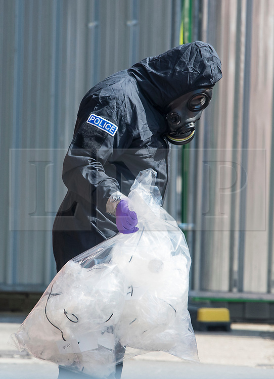 © Licensed to London News Pictures. 06/07/2018. Salisbury, UK. A member of a police specialist team wearing a hazmat suit is seen carrying bagged up materials while leaving John Baker House in Salisbury, Wiltshire an area visited by two people who are in critical condition after being exposed to the Novichok nerve agent. Dawn Sturgess, 44, and Charlie Rowley, 45 have been confirmed as having come in to contact with the deadly agent after samples were sent to the MoD's Porton Down laboratory. Former Russian spy Sergei Skripal and his daughter Yulia were poisoned with Novichok nerve agent in nearby Salisbury in March 2018 causing diplomatic tentions between Russia and the UK. Photo credit: Ben Cawthra/LNP