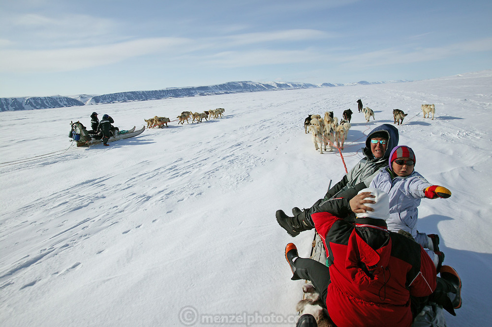 (MODEL RELEASED IMAGE). The Madsen family on a day of dogsled travel. When the snow crust is hard enough to ensure that the dogs won't break through, they can pull the half-ton weight of the sled for hours on end. On level ground, the animals pull at about the pace of a running human, but the sleds can whip down hills so fast that drivers must step on the brake at the rear of the sled to avoid running over their dogs. (Supporting image from the project Hungry Planet: What the World Eats.)