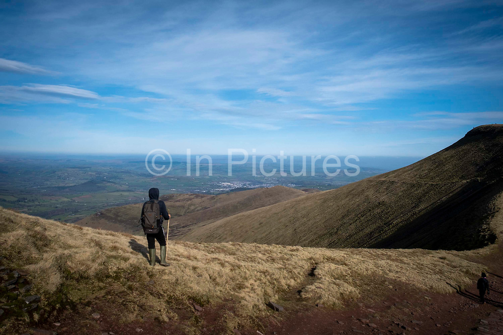 A child with a rucksack and walking stick stands admiring the landscape view from Pen Y Fan mountain range in Brecon Beacons National Park, Wales, Powys, United Kingdom.  Pen Y Fan is the highest point in the Brecon Beacons hill and mountain range in South Wales. The National Park was established in 1957 due to the spectacular landscape which is rich in natural beauty and is run by the National Trust.