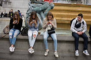 Three teenage girls are lost in the world of smartphone apps and messaging, in Trafalgar Square. While in a very busy environment in the capital's main square in central London and with the admiring glance of a young man alongside, the teenagers obsessively tweet and message their friends at home, completely unaware of their surroundings, absorbed in the functions of their devices and their young lives. Sitting on the walls of the fountains, they are isolated from each other and the noise around them. In the backgrounds are tourists enjoying the architecture and ambience of a busy city.