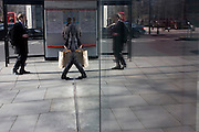 Humerous reflection in plate glass of a pedestrian walking through a shopping complex in the financial City of London.