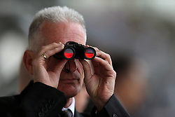 A spectator looking though binoculars during the Manny Mercer Apprentice Handicap during Royal Ascot Trials Day at Ascot Racecourse.