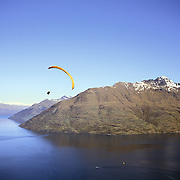 A paraglider flies above Queenstown, New Zealand, with the snow capped mountain range providing a stunning backdrop. Queenstown is nestled on the shores of the crystal clear waters of Lake Wakatipu in the Central Otago region of the South Island of New Zealand. Queenstown is New Zealand's premier tourist destination providing an abundance of year round outdoor activities for both young and old. Queenstown, Central Otago, South Island, New Zealand. Photo Tim Clayton.