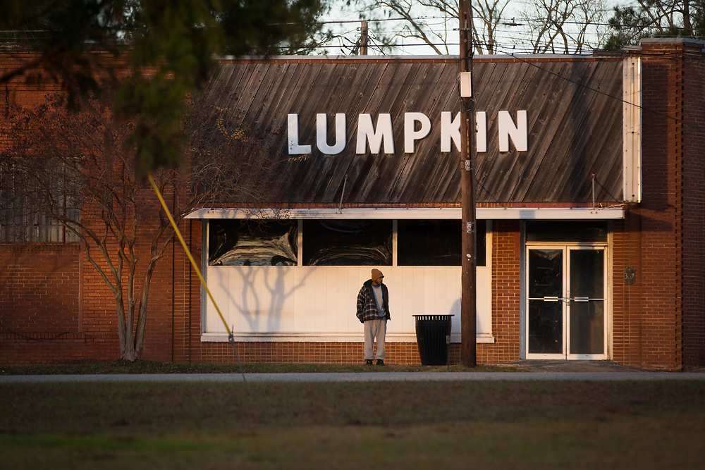 A man stands outside one of many shuttered business in downtown Lumpkin, Ga., on Thursday, Jan. 14, 2016. Shot for a story about Shawn Toussaint, who is in federal custody at the Stewart Detention Center, where immigrants are detained, in Lumpkin and was denied release during a hearing Thursday. Photo by Kevin D. Liles for NPR
