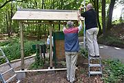 Nederland, Arnhem, 22-5-2014Open dag van hoeve, zorghoeve, Klein Mariendaal . De hoeve is een centrum voor mensen met een geestelijke beperking en daardoor een afstand tot de arbeidsmarkt . Gepensioneerde Vrijwilligers uit de buurt maken een toegangsbord bij de toegang tot de boerderij . Foto: Flip Franssen