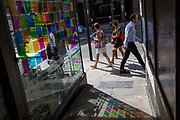 Passers-by walk past coloured light from a corner cafe reflected on the pavement in Fleet Street in the City of London, the capitals financial district aka the Square Mile, on 22nd August 2019, in London, England.