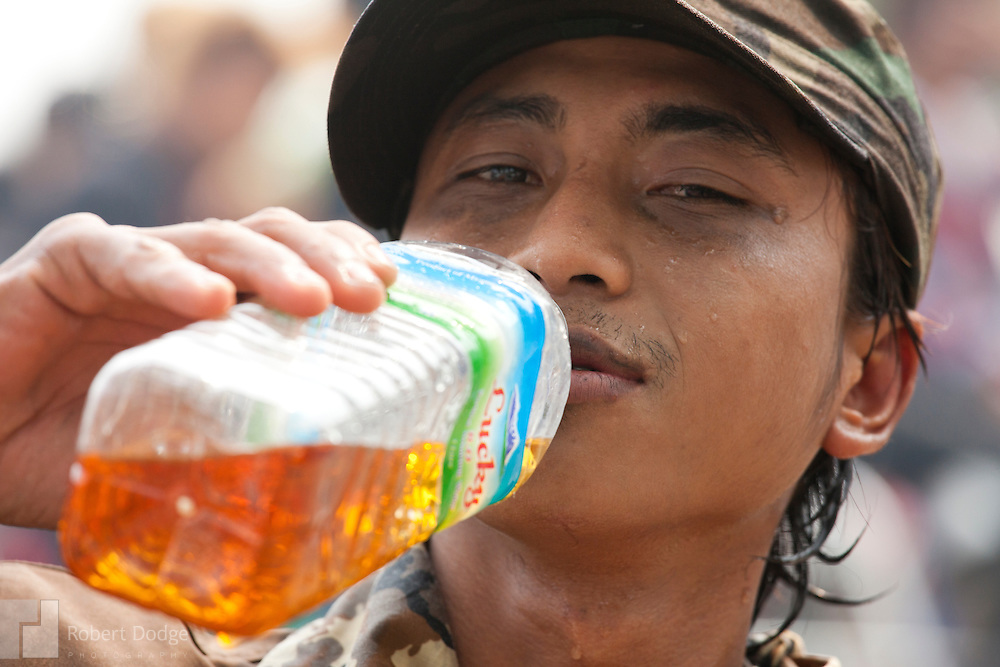 Mandalay, Myanmar- April 14, 2013: Is that tea or something stronger? Only this young man knows for sure as he takes a break during Myanmar's Thingyan Water Festival. Thingyan is held in April, one of the hottest months of the year in Myanmar. The water festival marks the country's New Year celebration and the festival includes lots of drinking, singing, dancing and theater. Wherever you are you are likely to get doused with water as the Burmese see this as a cleansing of the previous year's sins and bad luck and a blessing for good luck and prosperity in the year ahead. In the major cities of Mandalay and Yangon, large platforms are erected along major roadways and are equipped with high powered water hoses. The platforms, sponsored by large corporate donors, also have dance stages and play the latest pop and hip hop music. Thousands of residents pour into the streets by foot, motorbike and flatbed truck to get hosed under the platforms while they drink and dance. Many of the young celebrants wear their best clubbing clothes. And many of the party goers are men, having left their wives and girlfriends at home.