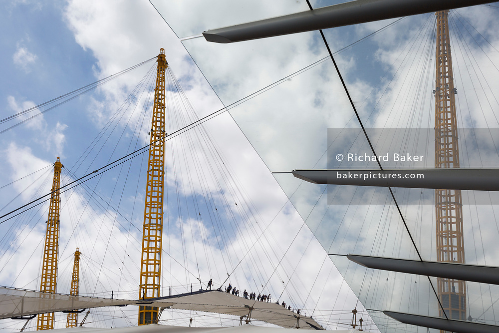 Walkers climb the steep dome of the O2 Arena, on 24th June 2017, Greenwich Peninisular, London. Designed and developed by the original architects of The O2 music and entertainment venue (once called The Millennium Dome), climbers are challenged on a 30° ascent on the 380 metres fabric walkway 52m above the ground. Climbers are rewarded for their efforts with panoramas of the City, Greenwich Park and such landmarks as the Tower of London, the Observatory and The Shard.