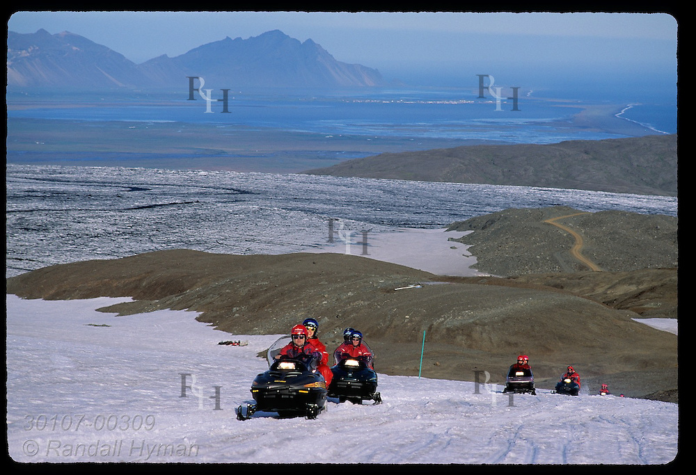 Snowmobilers race up Vatnajokull glacier on two-hour Glacier Tours trip as southeast coast disappears behind them; Iceland.
