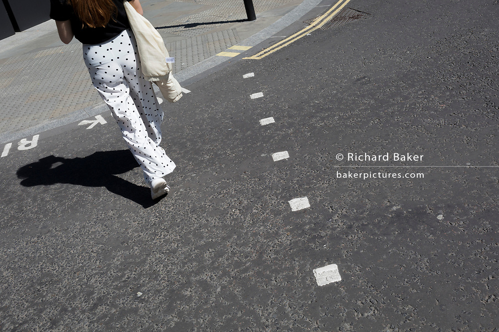 A lady wearing trousers with a dotted pattern crosses the road in the City of London, the capital's ancient, financial district, on 14th May, in London, England.