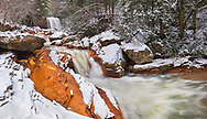 Winter visits Douglas Falls in Thomas, West Virginia, with a layer of snow covering the orange, iron laden sandstone created from acid mine drainage.