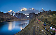 Sunrise illuminates the Cordillera Huayhuash above Carhuacocha lake campground (13,600 feet) in the Andes Mountains, Peru, South America. Peaks from left to right are: Siula Grande, Yerupaja Grande (6635 m or 21,770 ft, highest point in the Amazon watershed), Yerupaja Chico, and Mount Jirishanca (Icy Beak of the Hummingbird). Day 3 of 9 days trekking around the Cordillera Huayhuash. This panorama was stitched from 4 overlapping photos.