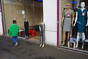 Weird street scene with silver trousers outside a shop as people pass by. Barons Court, London, UK. A pair of sparkly jeans standing outside a cheap clothes store on a half mannequin from the waist down. A strange situation as pessers by somehow interact with the half dummy.