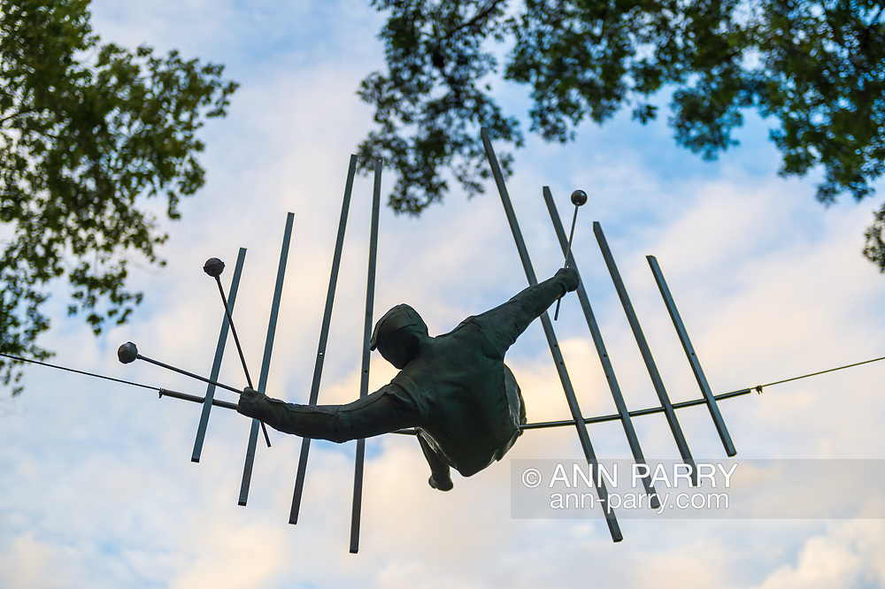 """Old Westbury, New York, U.S., September 1, 2019. """"The Last Show False Tone"""" is one of 33 outdoor sculptures by Jerzy Kedziora (Jotka), b. 1947 in Poland, and his Balance in Nature art is on view at historic Old Westbury Gardens in Long Island, until October 20, 2019. Seen almost silhouetted by the sky, the life-size, bronze resin balancing sculpture, high on a wire suspended between trees, is of a musician holding three mallets to hit notes on 8 bars."""