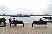 Nederland, Tolkamer, 8-4-2015Twee oudere mannen rusten uit op een bankje aan de Waal, Rijn en kijken naar de schepen die voorbijkomen.Foto: Flip Franssen/Hollandse Hoogte