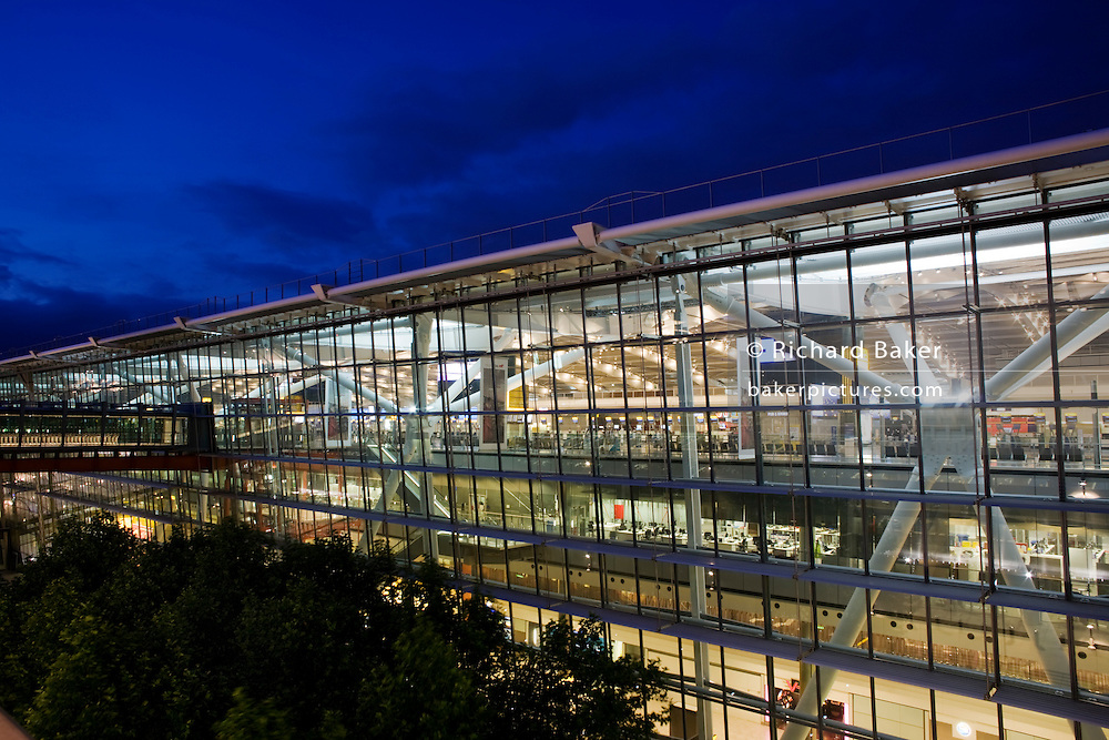 "Seen from the outside in early evening, the glass walls and glowing architecture of Heathrow Airport's Terminal 5, the largest free-standing building in the UK. Created by the Richard Rogers Partnership (now Rogers Stirk Harbour and Partners) and opened in 2008 after a cost of £4.3 billion, Terminal 5 has the capacity to serve around 30 million passengers a year. From writer Alain de Botton's book project ""A Week at the Airport: A Heathrow Diary"" (2009). ..."