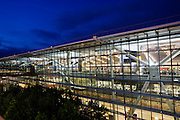 """Seen from the outside in early evening, the glass walls and glowing architecture of Heathrow Airport's Terminal 5, the largest free-standing building in the UK. Created by the Richard Rogers Partnership (now Rogers Stirk Harbour and Partners) and opened in 2008 after a cost of £4.3 billion, Terminal 5 has the capacity to serve around 30 million passengers a year. From writer Alain de Botton's book project """"A Week at the Airport: A Heathrow Diary"""" (2009). ..."""