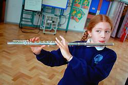 Primary schoolgirl playing flute at school UK