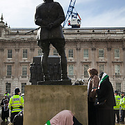 A devout female muslim prays behind the statue of General Montgomery of Al Amein in Whitehall during speeches an Anti-Assad Syrian demonstration held in Whitehall, Central London. The demonstration was called by the Syrian Community in the UK under the head lines; Syrians are being killed in a genocide and the world is watching. Several hundreds gathered opposite Downing Street 10 calling for Syrians to unite and the world to intervene.