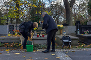 Two ladies clean a grave at Rakowicki cemetery in Krakow, Poland 2019.