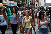 Girls out shopping at Brick Lane for the Sunday Market. Many people come to sell their cast-off clothes and belongings to raise some cash. Official stalls selling clothers, food and all manner of crafts and junk make up the mainstay of the market though. These unofficial sellers though give the market it's unique atmosphere. This market is a weekly event in London's East End.