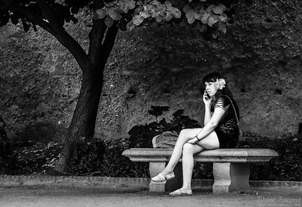 Woman on a bench with a telephone.
