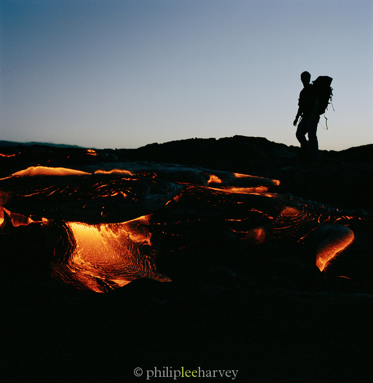 A hiker stands watching a lava flow in Hawaii Volcanoes National Park, Hawaii, USA