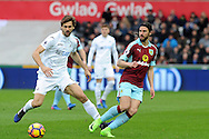 Burnley's George Boyd (r) passes whilst under pressure from Swansea's Fernando Llorente. Premier league match, Swansea city v Burnley at the Liberty Stadium in Swansea, South Wales on Saturday 4th March 2017.<br /> pic by  Carl Robertson, Andrew Orchard sports photography.