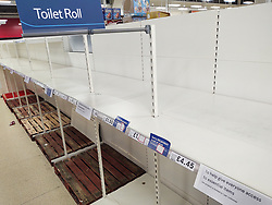 © Licensed to London News Pictures. 18/03/2020. Salford, UK. The Tesco branch , which normally opens until Midnight, closes two hours early as stock shortages become evident . A branch of Tesco in Salford has sold out of all stock of all toilet paper products as customers panic buy essentials , including bread , pasta and hand sanitiser , in fear of a lockdown and shortages . Today the British Government announced further measures to combat the spread of Coronavirus ( COVID-19 ) , including school closures and further state support for those affected . Photo credit: Joel Goodman/LNP