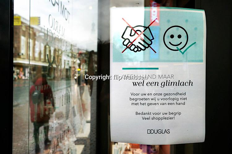 Nederland, Nijmegen, 13-3-2020  In de winkelstraten is het een stuk rustiger als normaal . Veel winkels hebben bij de ingang een mededeling die verwijst naar het handen schudden of afstand houden van het personeel naar de klant toe . Foto: Flip Franssen