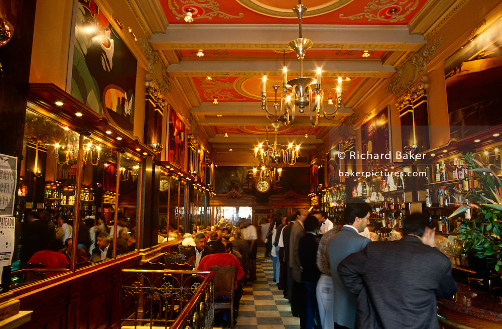 The busy atmosphere of mid-day Portuguese society inside the famous Café A Brasileira do Chiado in central Lisbon.