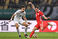 """Gareth Bale, right, of Wales national football team kicks the ball to make a shoot against Sebastian Coates of Uruguay national football team in their final match during the 2018 Gree China Cup International Football Championship in Nanning city, south China's Guangxi Zhuang Autonomous Region, 26 March 2018.<br /> <br /> Edinson Cavani's goal in the second half helped Uruguay beat Wales to claim the title of the second edition of China Cup International Football Championship here on Monday (26 March 2018). """"It was a tough match. I'm very satisfied with the result and I think that we can even get better if we didn't suffer from jet lag or injuries. I think the result was very satisfactory,"""" said Uruguay coach Oscar Tabarez. Wales were buoyed by a 6-0 victory over China while Uruguay were fresh from a 2-0 win over the Czech Republic. Uruguay almost took a dream start just 3 minutes into the game as Luis Suarez's shot on Nahitan Nandez cross smacked the upright. Uruguay were dealt a blow on 8 minutes when Jose Gimenez was injured in a challenge and was replaced by Sebastian Coates. Inter Milan's midfielder Matias Vecino of Uruguay also fired at the edge of box from a looped pass but only saw his attempt whistle past the post. Suarez squandered a golden opportunity on 32 minutes when Ashley Williams's wayward backpass sent him clear, but the Barca hitman rattled the woodwork again with goalkeeper Wayne Hennessey well beaten."""