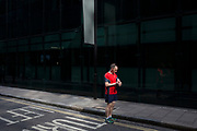 Man out running stops in the street to check his wristwatch device in London, England, United Kingdom.