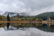 Reflections of autumn foliage and Mount Maxwell on a rainy day along the shore of Blackburn Lake on Salt Spring Island, British Columbia, Canada