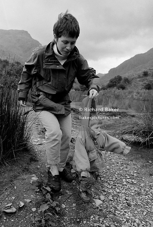 """First shoes in Wales."" An eleven month-old infant tries to walk in her first pair of proper rigid shoes whilst on holiday in Snowdonia, North Wales UK. Tentatively taking a few unconfident steps the young girl  cries out in surprise, almost falling over. Her mother instinctively grabs her coat hood before she topples into into the pebbles and soft mud of a river bed which would soil her clean clothes. We see a mother preventing her daughter from getting dirty and from hurting herself, a fast reaction to stop injury on a small child. This is from a documentary series of pictures about the first year of the photographer's first child Ella. Accompanied by personal reflections and references from various nursery rhymes, this work describes his wife Lynda's journey from expectant to actual motherhood and for Ella - from new-born to one year-old."