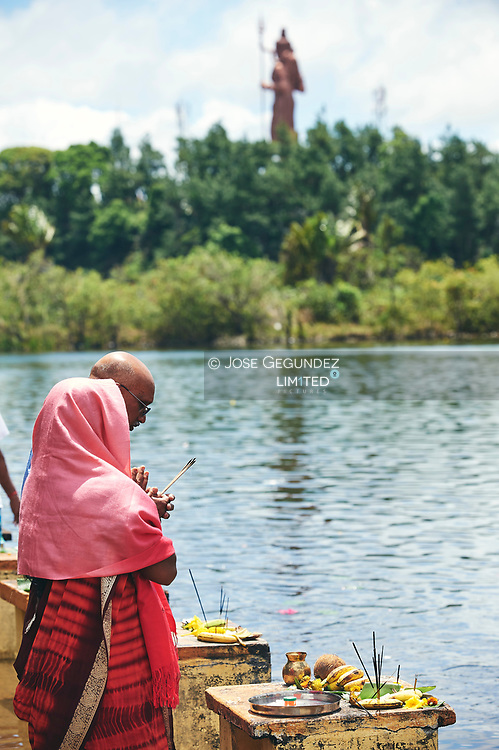 Mauritius Island. Grand Bassin. A couple of hindus praying at Gran Bassin with a Shiba statue at Background, the second largest in the world
