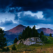 The Sawatch Range Peaks glow lightly during sunset after a thunderstorm near Eagle, Colorado.