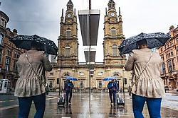 Glasgow, Scotland, UK. 27 June, 2020.  Heavy rain in Glasgow city centre as public with umbrellas walk past shop window   Iain Masterton/Alamy Live News